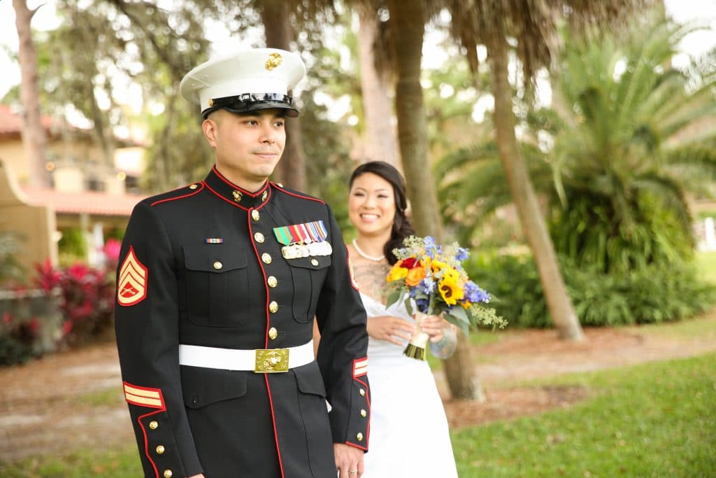 Bride approaching military groom from behind to surprise him