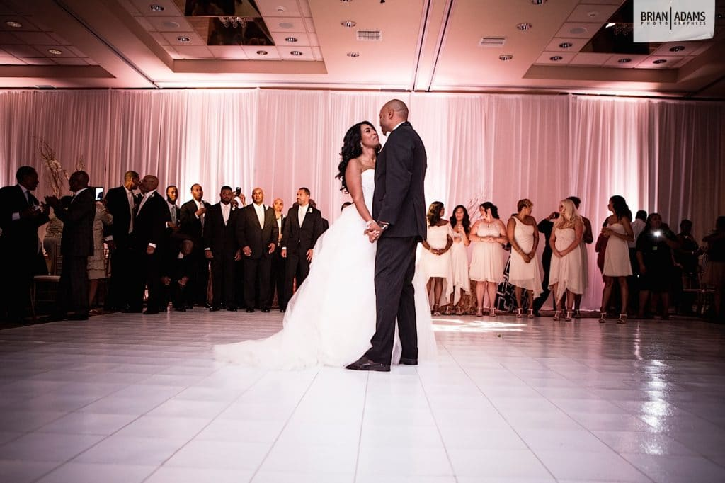 Bride and groom share first dance on white dance floor