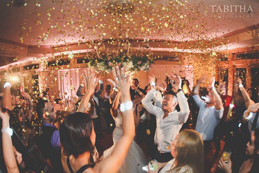 Wedding guests party under shower of gold confetti