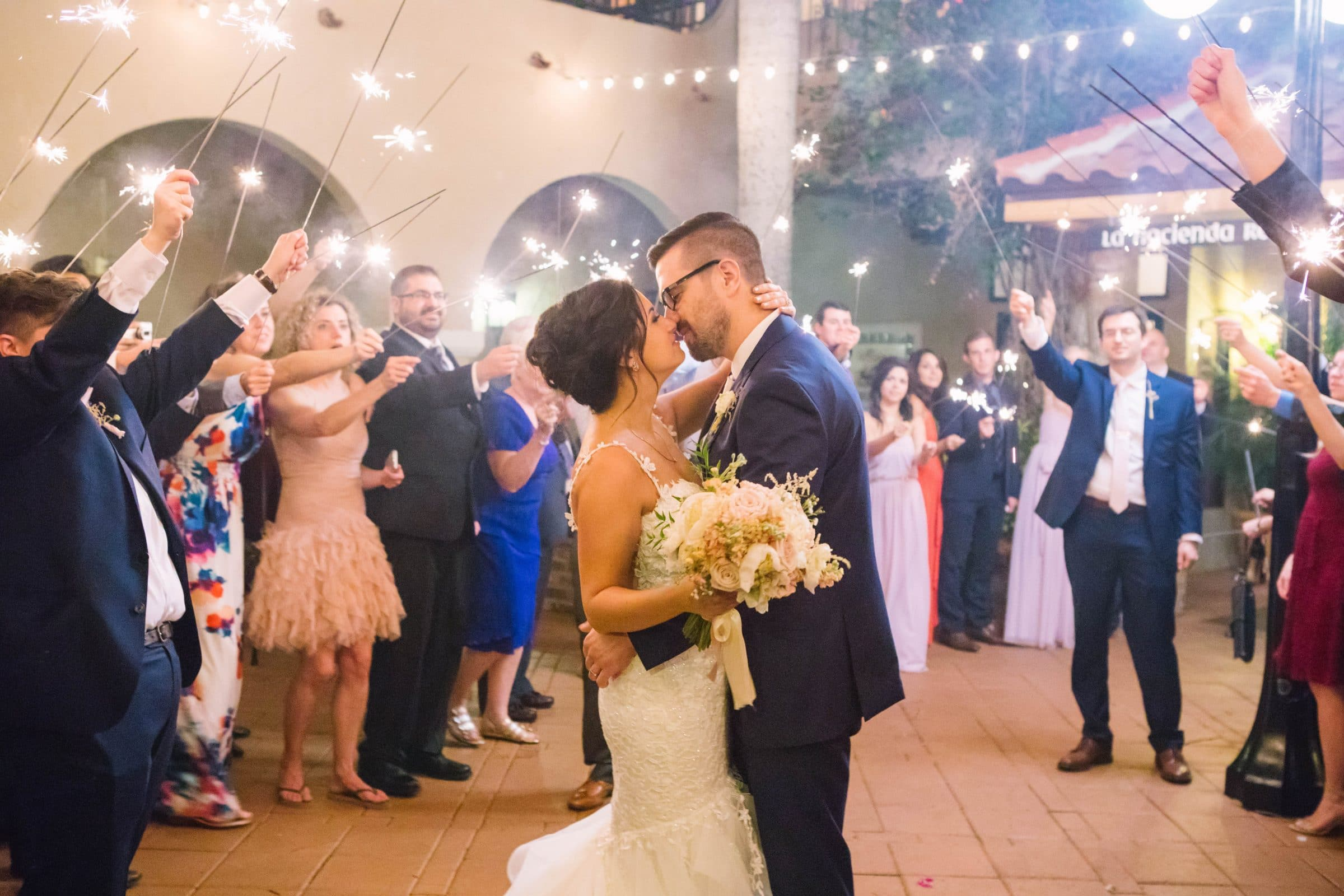 Bride and groom kissing in Spanish courtyard during sparkler sendoff