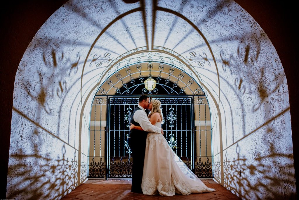 bride and groom kissing in hallway lit with wrought iron shadows
