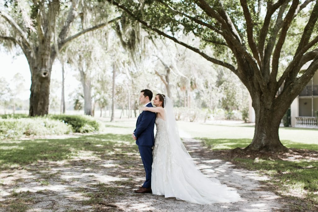 Bride hugging groom from behind under large oak tree