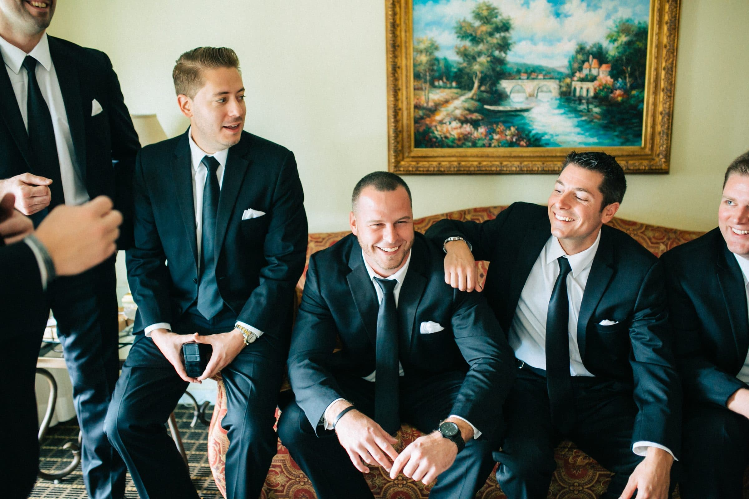 Groom and groomsmen chatting on couch