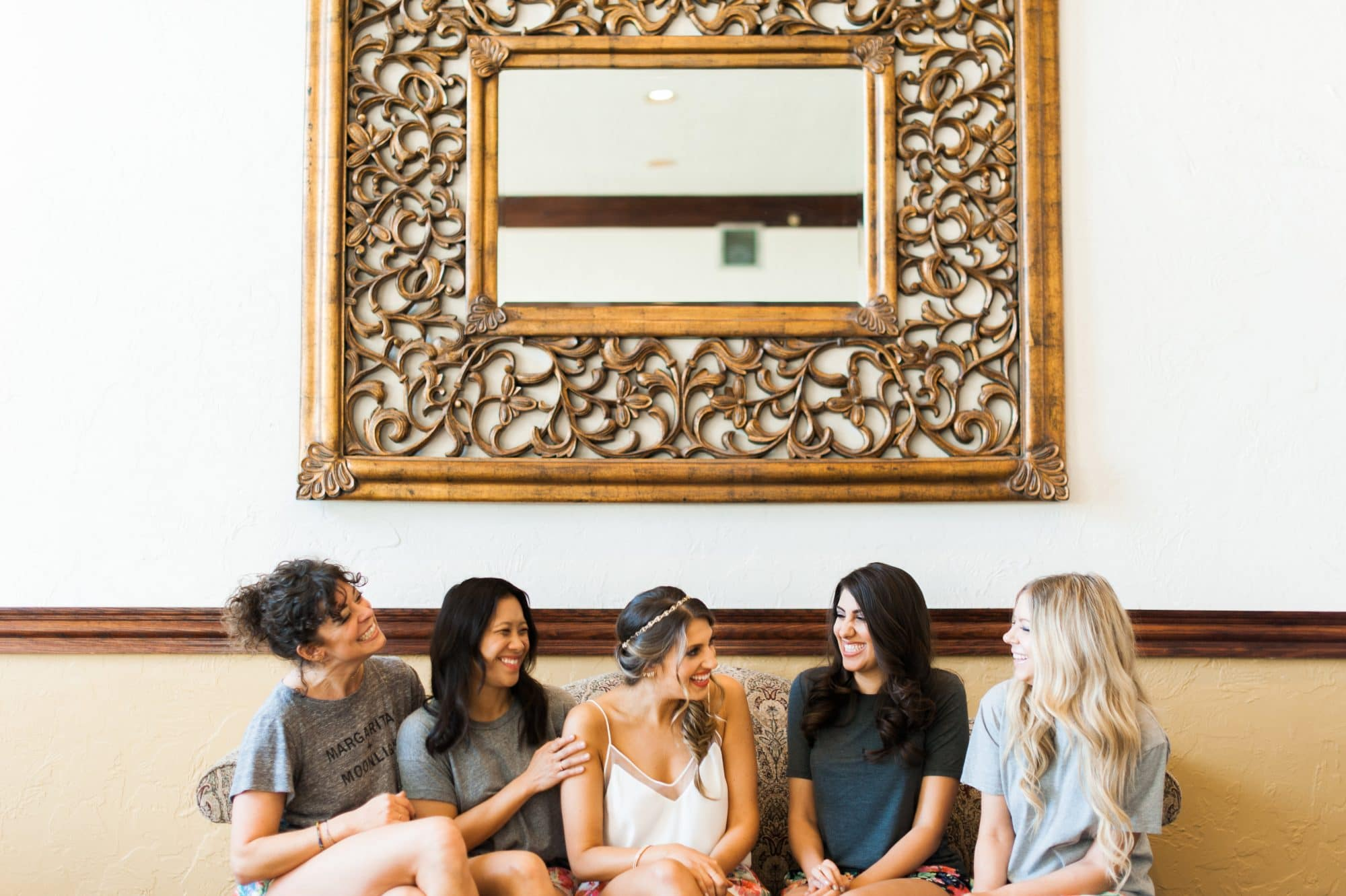 Bride and bridesmaids chatting on couch