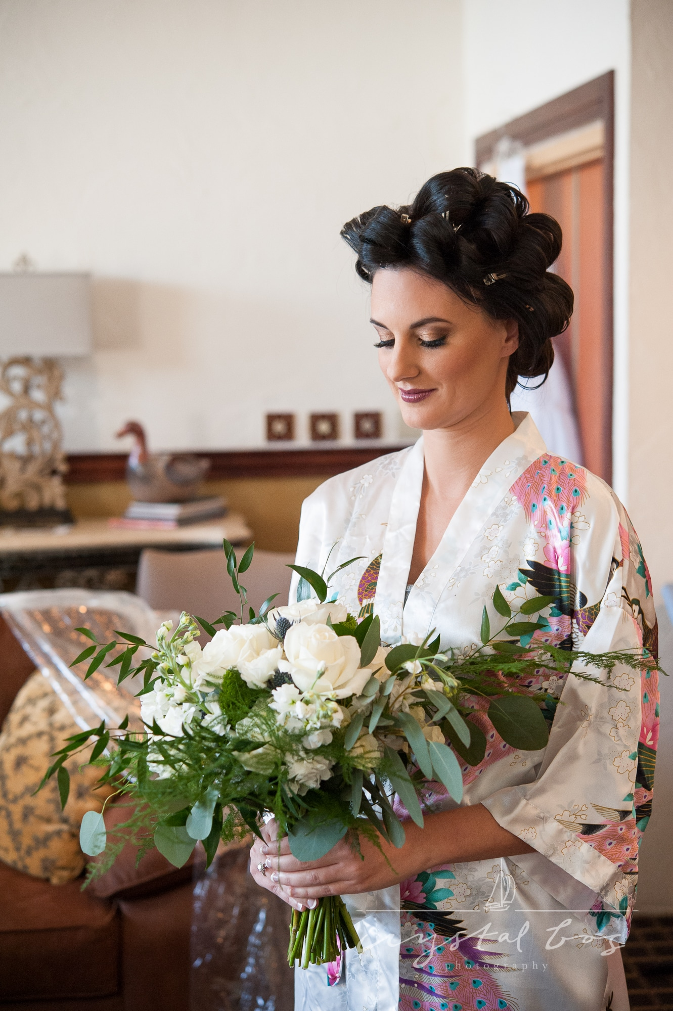 Bride in floral robe and curlers looking at her bouquet