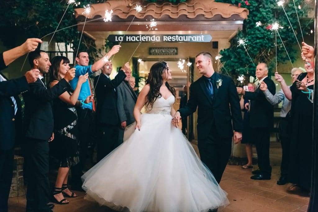 Bride and groom walking out of La Hacienda restaurant during sparkler sendoff