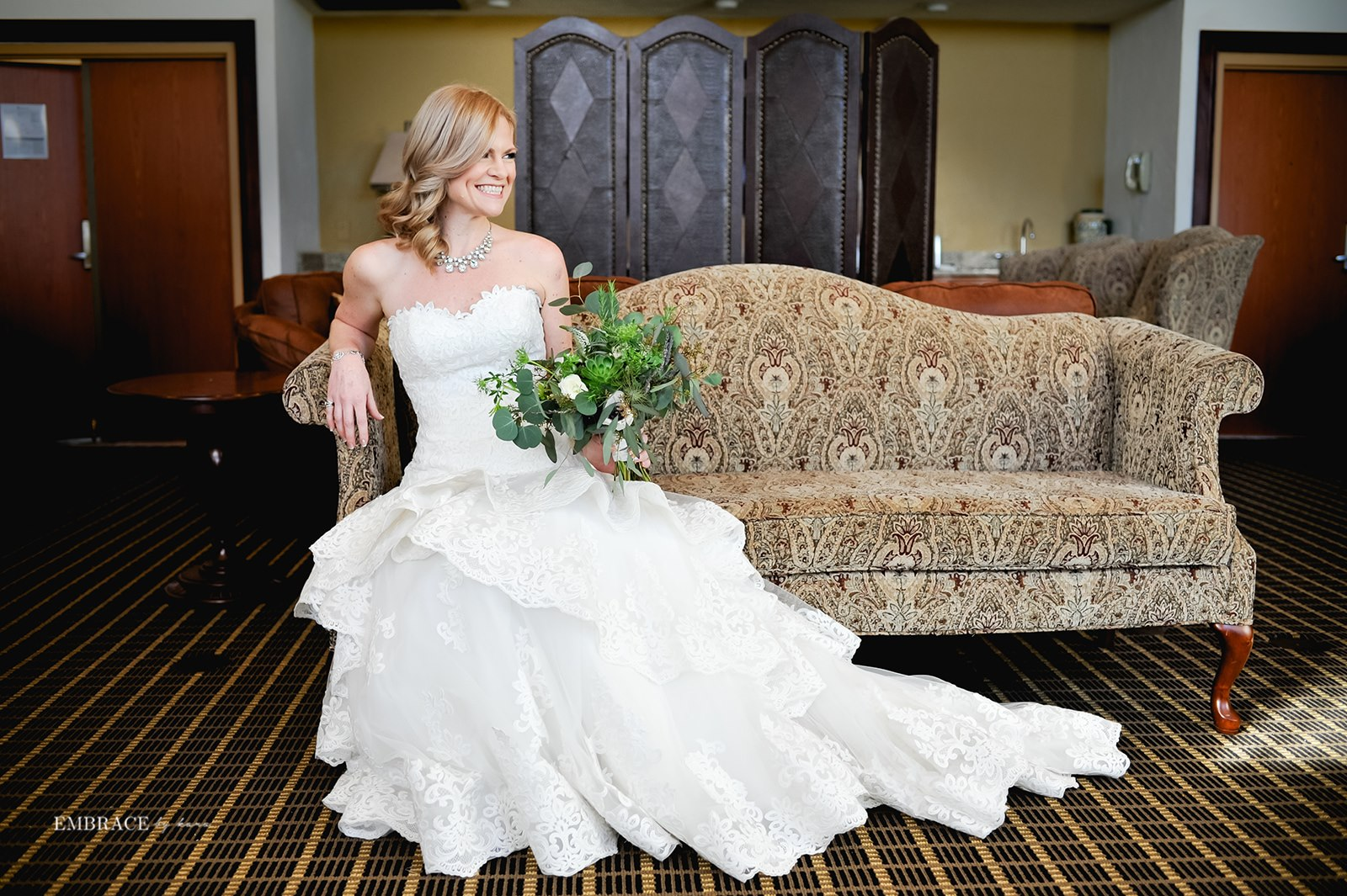 Bride lounging on couch with bouquet