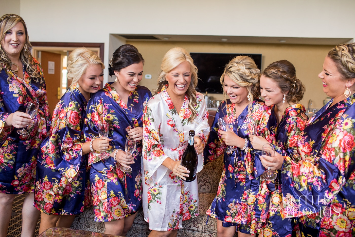 Bride opening champagne bottle while bridesmaids hold flutes