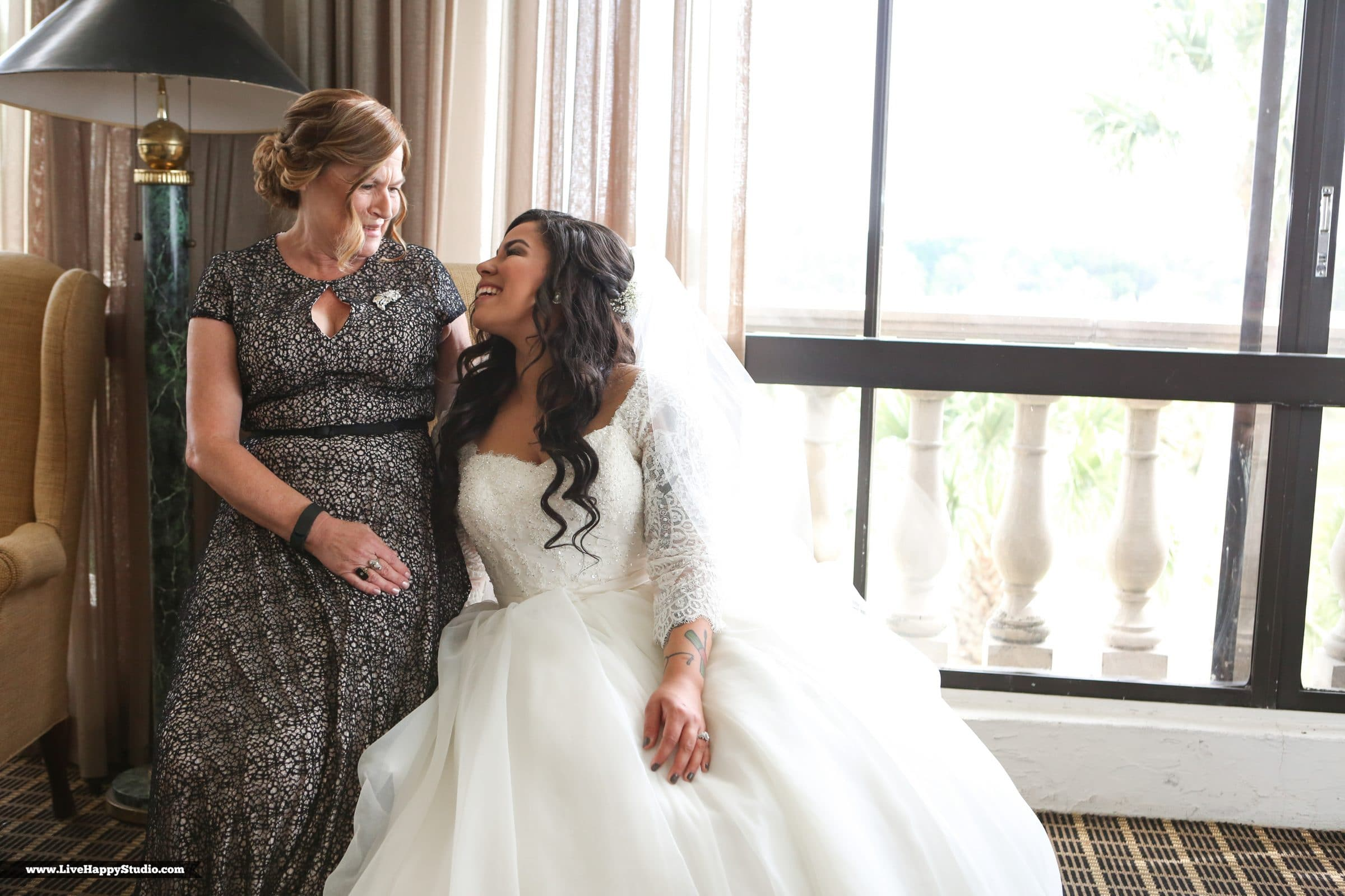 Bride laughing with mother in hotel room