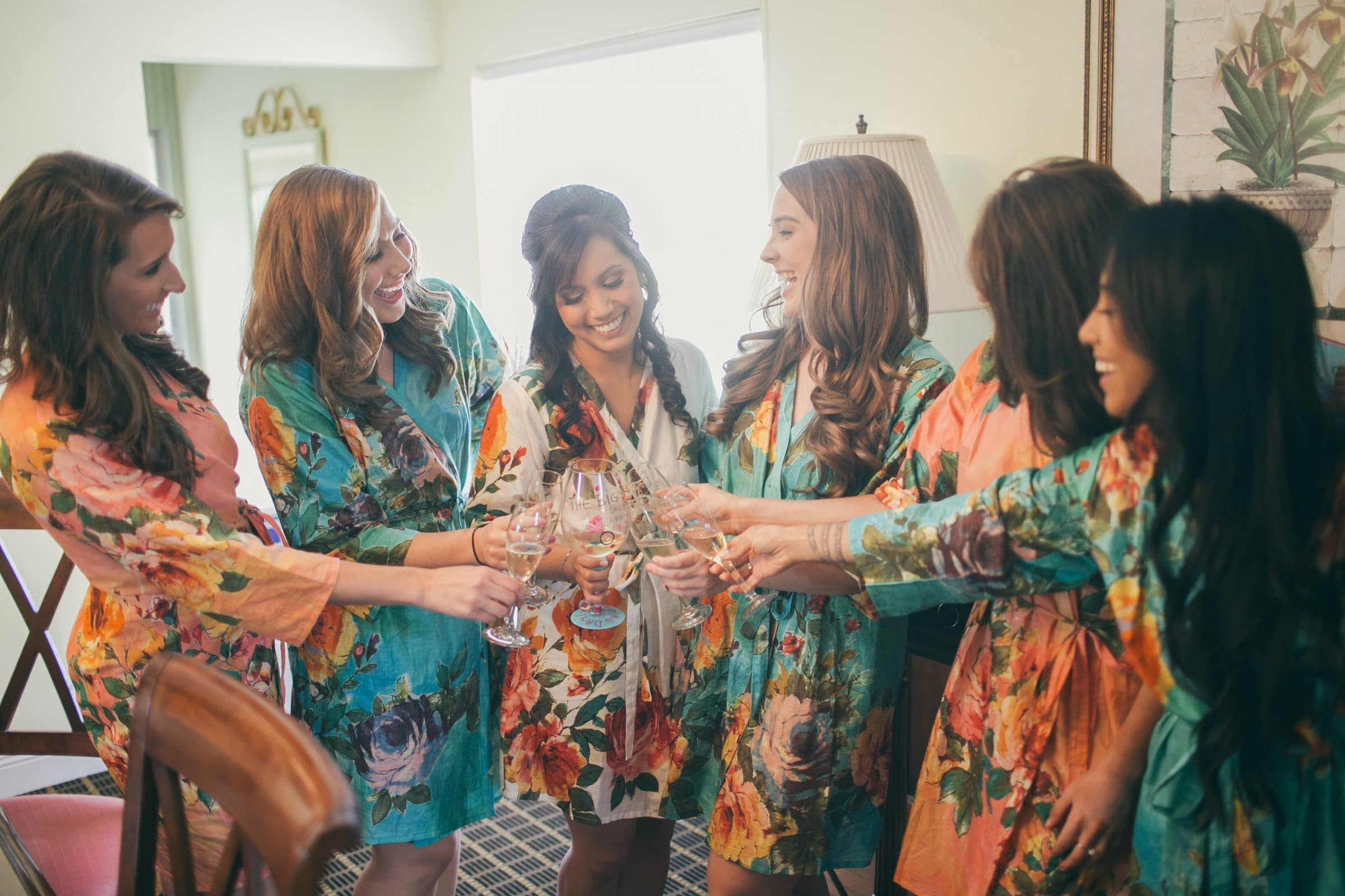 Bride and bridesmaids toasting in floral robes