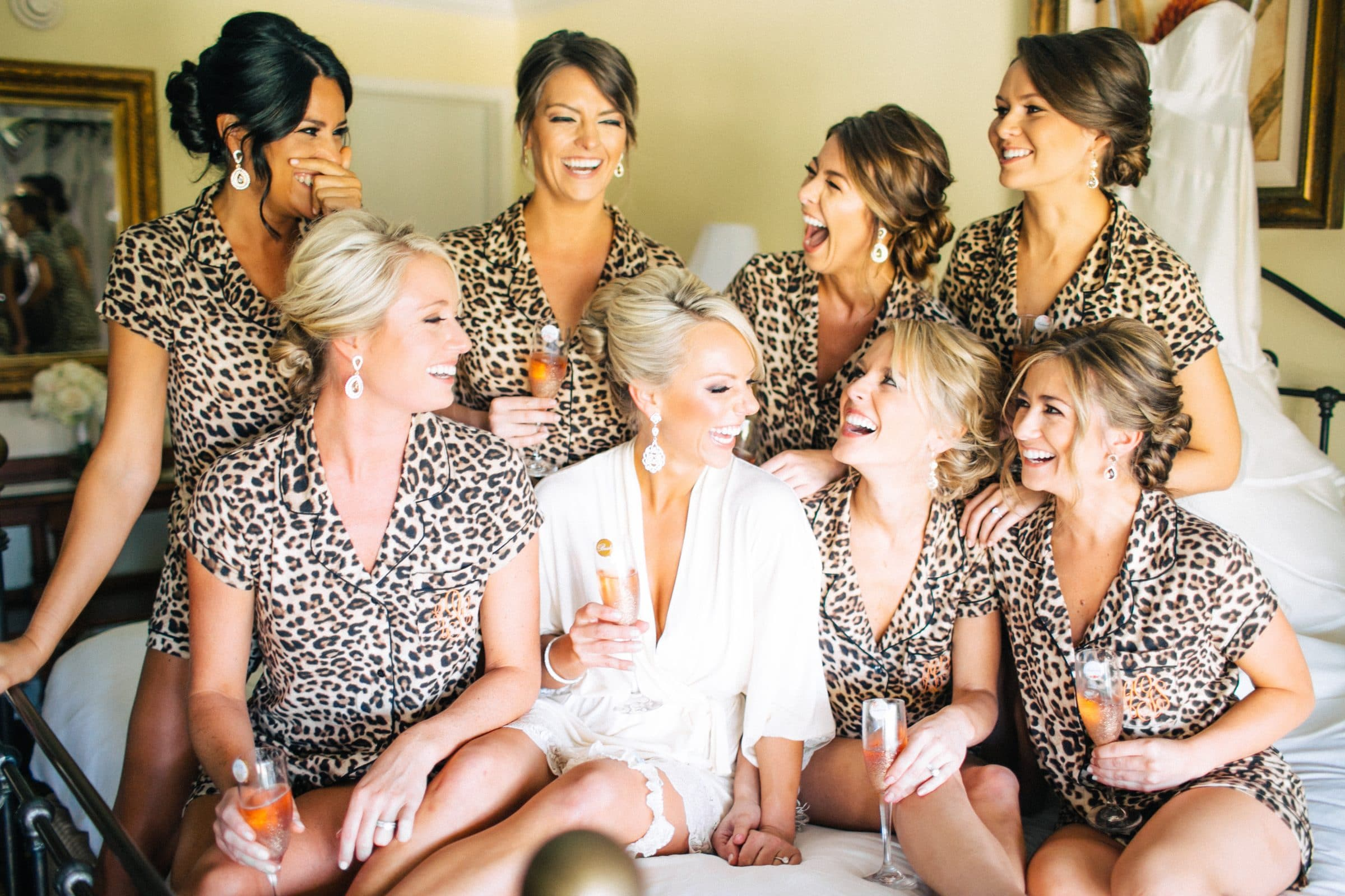 Bride and bridesmaids in leopard print pjs laughing while drinking champagne