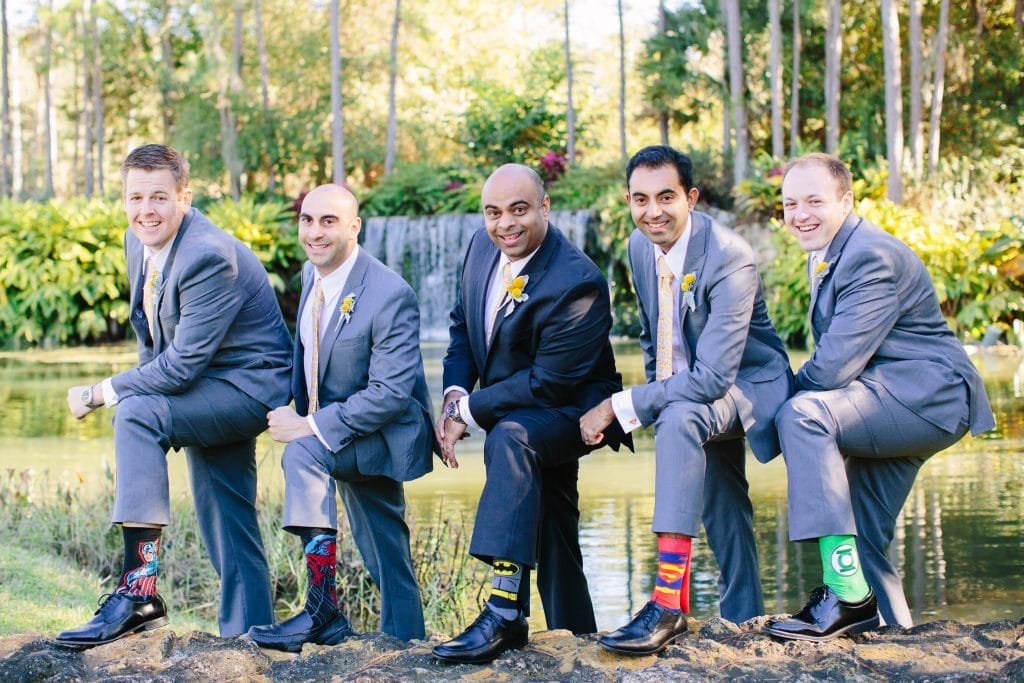 Groom and groomsmen showing off superhero socks