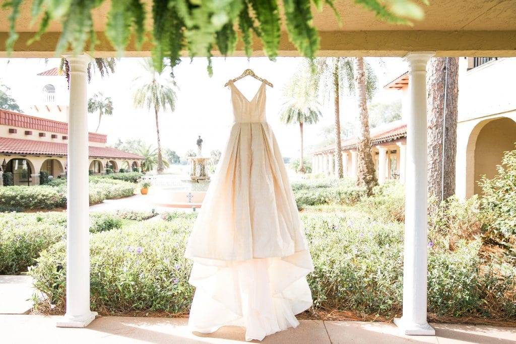 Wedding gown hung up under covered walkway