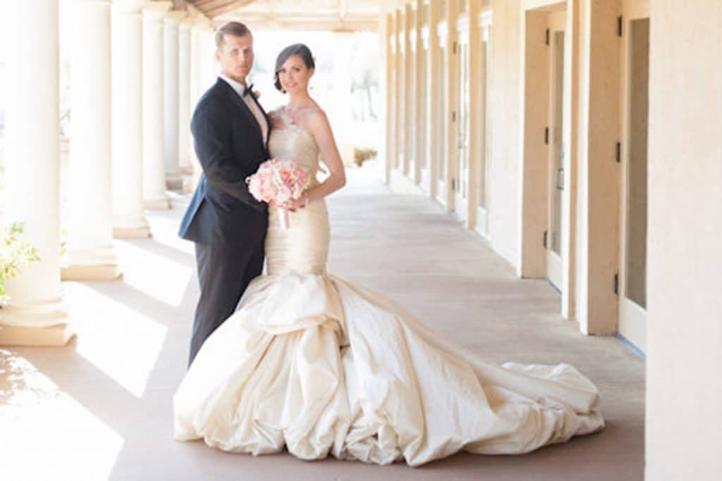 Bride with dramatic train standing next to groom under covered walkway