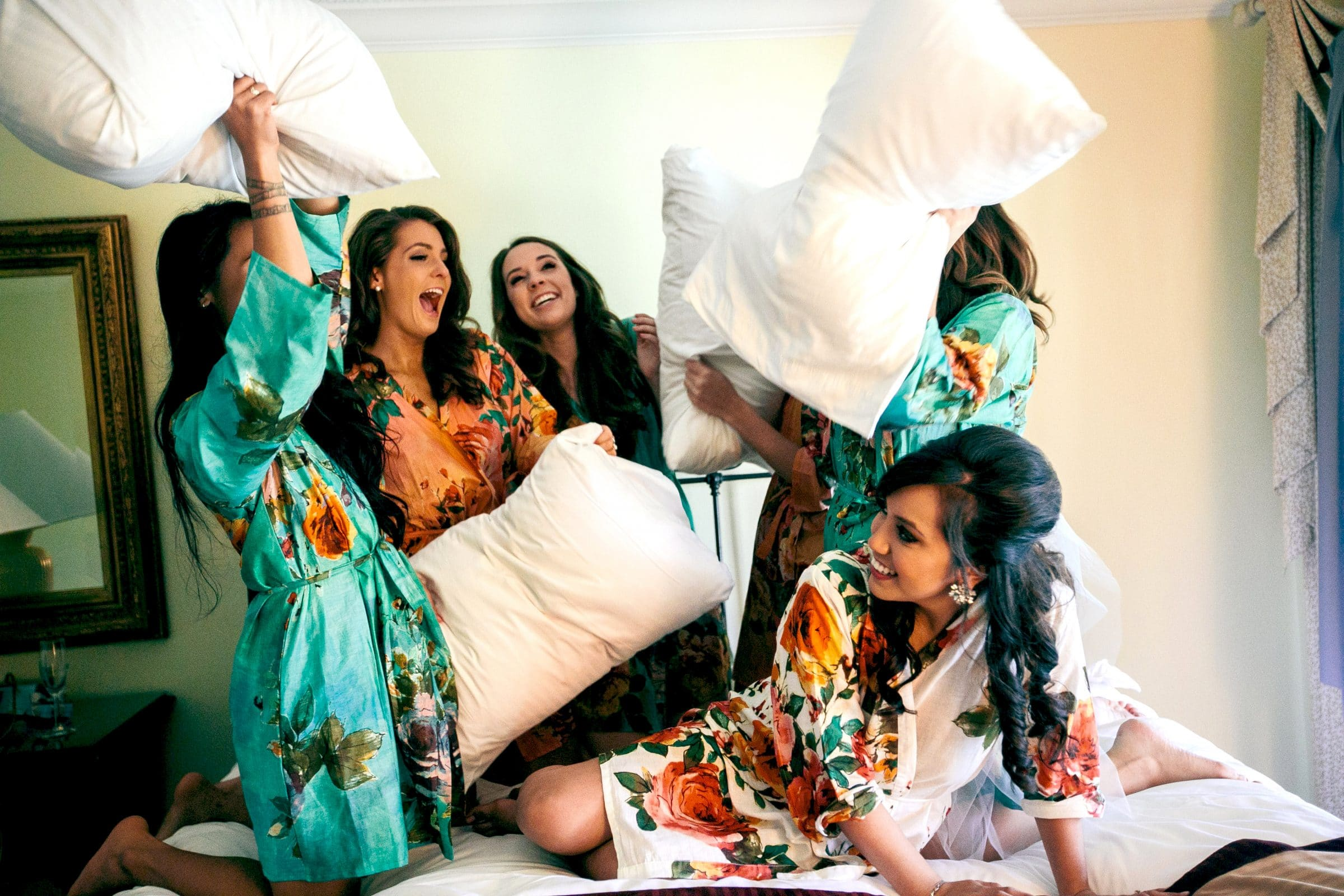 Bride and bridesmaids having pillow fight in ready room