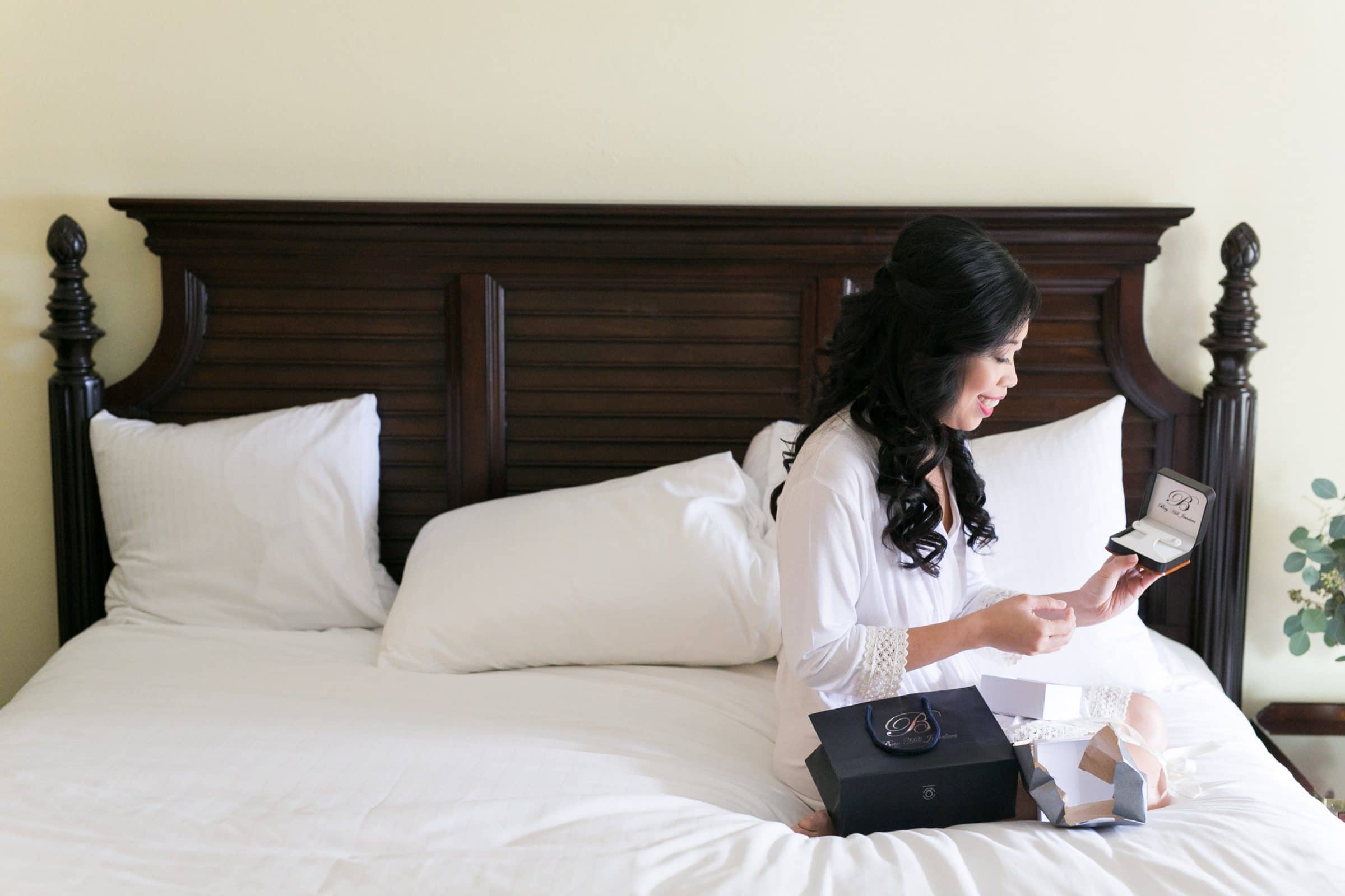 Bride opening jewelry box on bed