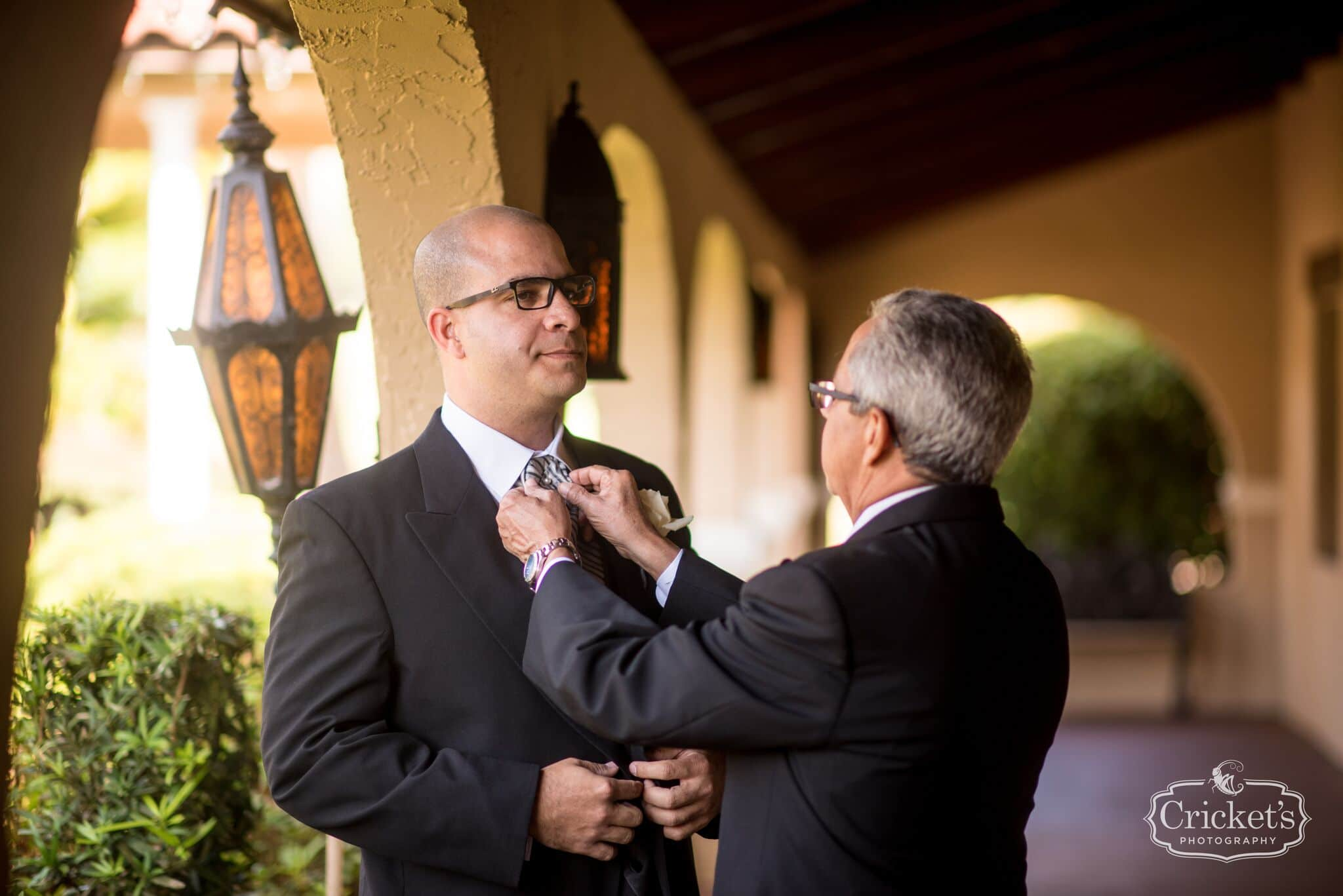 Groom's father adjusting groom's tie