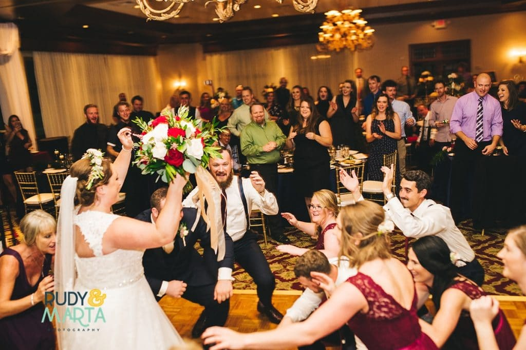 Bride and groom dancing with guests during wedding reception