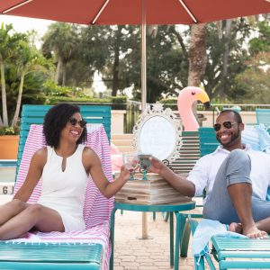 Man and woman toasting each other while relaxing on outdoor lounge chairs