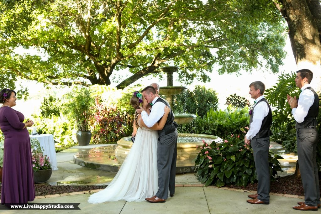 Bride and groom kiss next to vintage fountain in Legends Courtyard