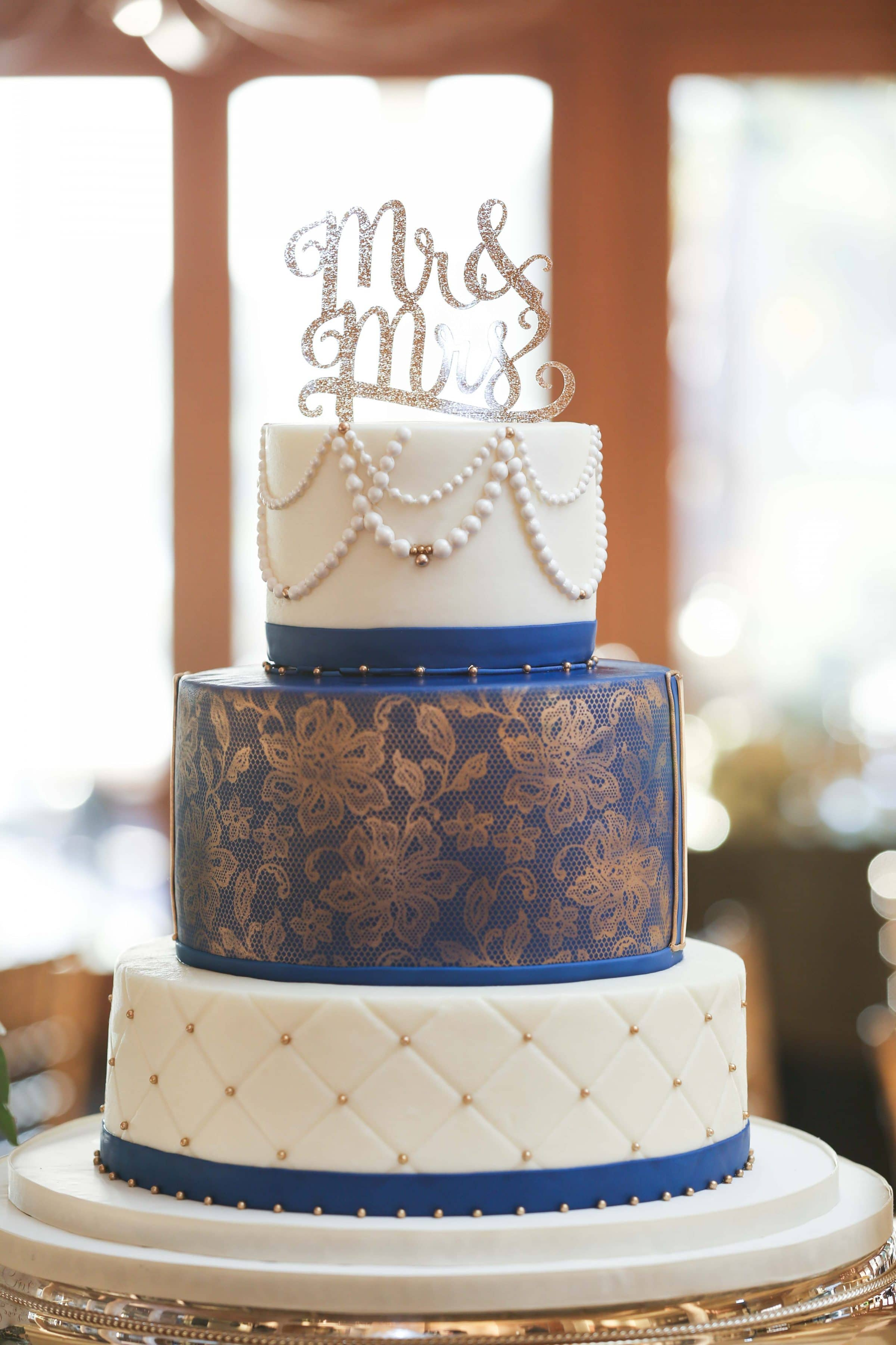 Glamorous blue and gold wedding cake with icing pearl garland