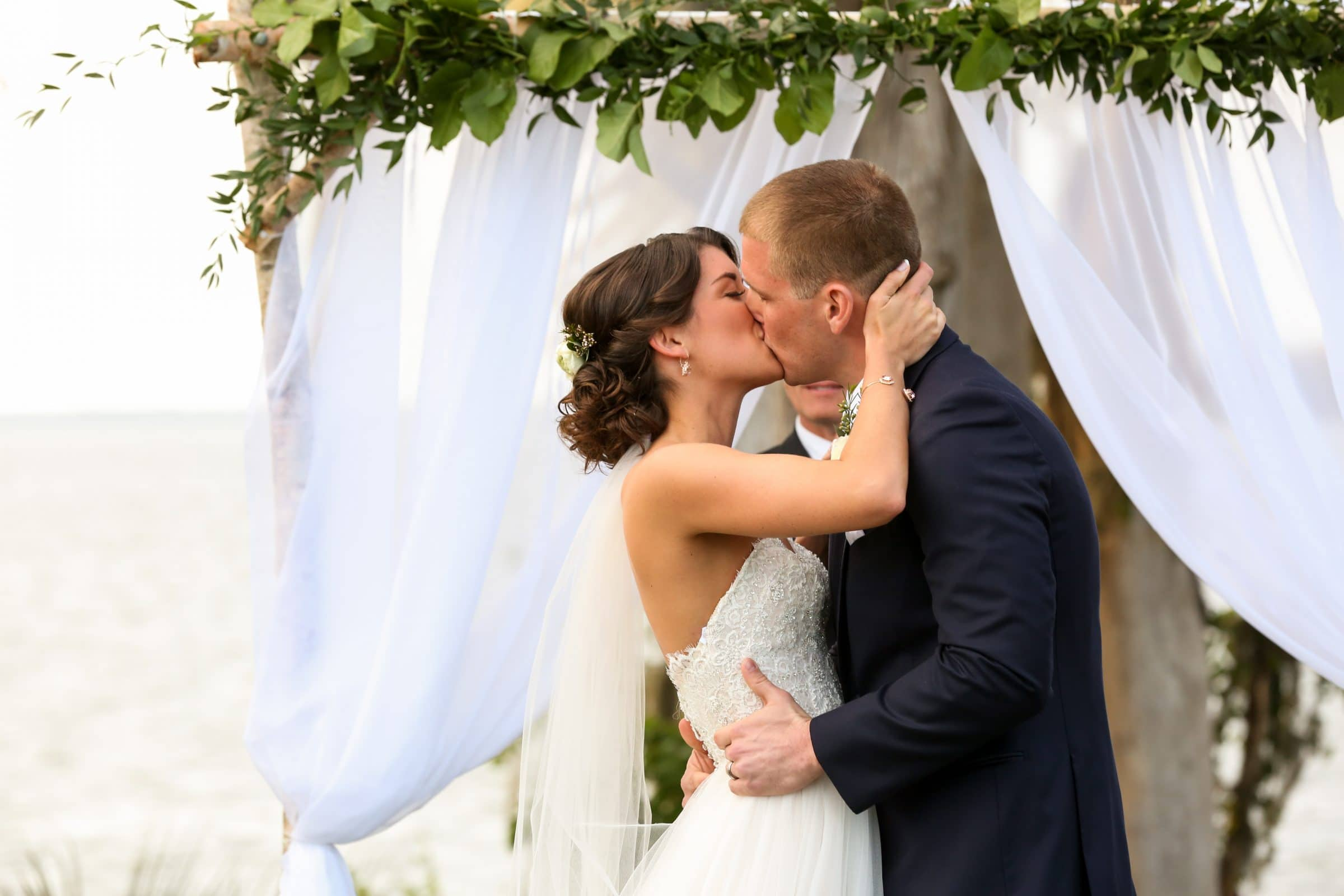 Bride and groom kiss in front of romantic fabric drapery