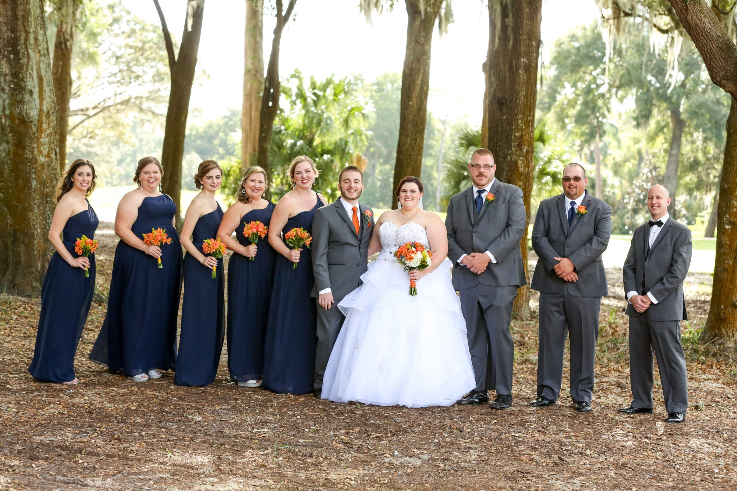 Wedding party with navy bridesmaids dresses and grey suits in Florida forest