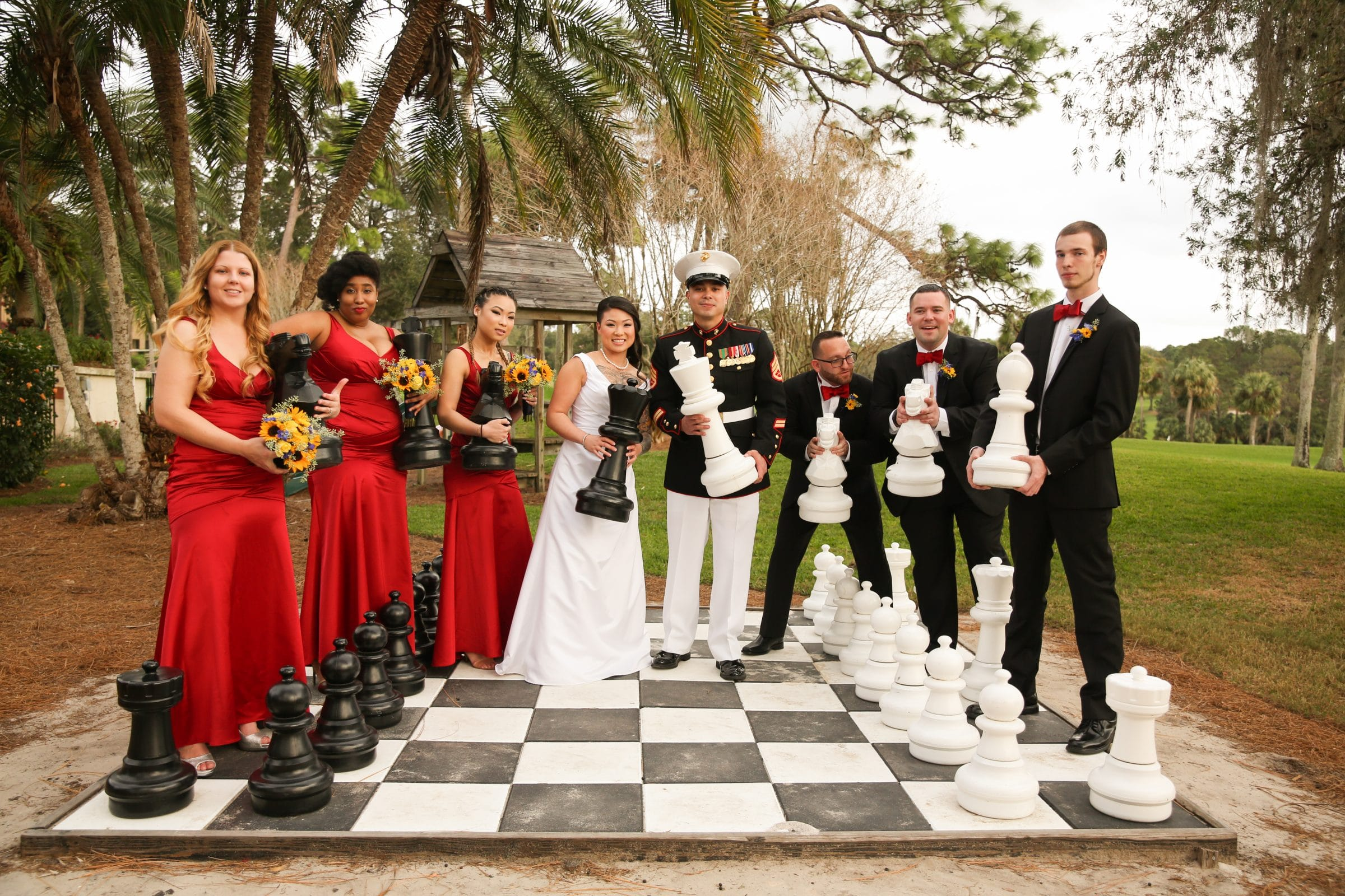 Wedding party holding chess pieces on giant chess board at Mission Inn Resort