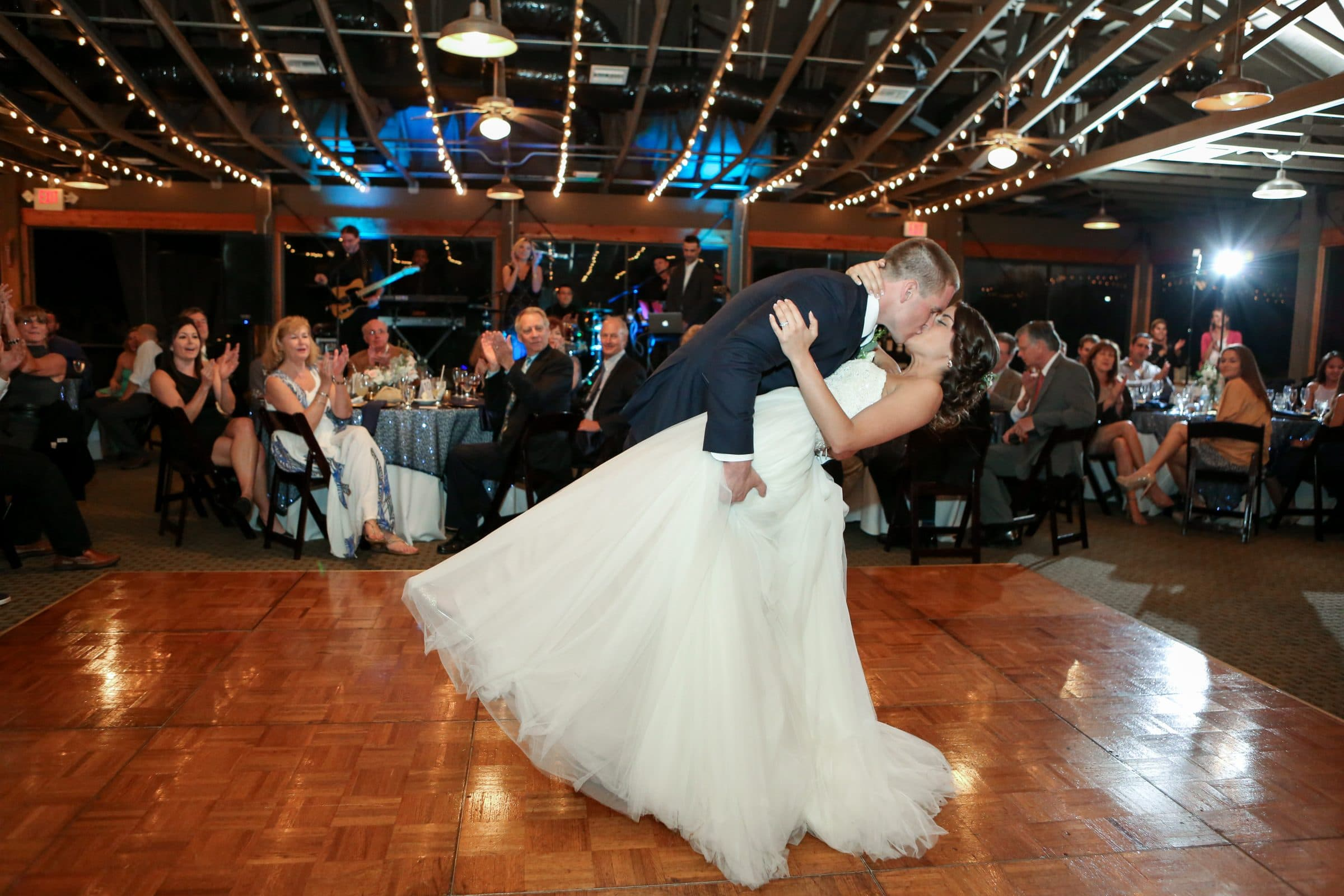 Groom dipping and kissing bride on dance floor at Marina del Rey
