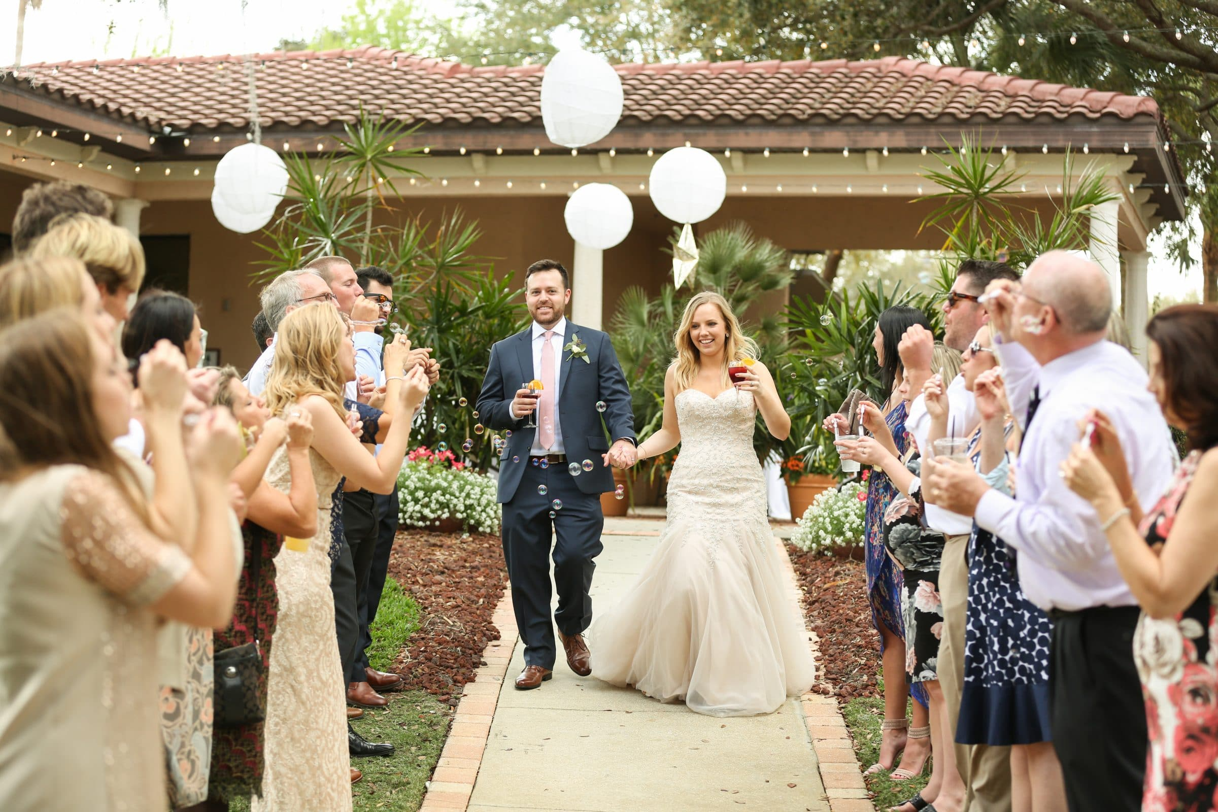 Bride and groom holding wine during bubble sendoff