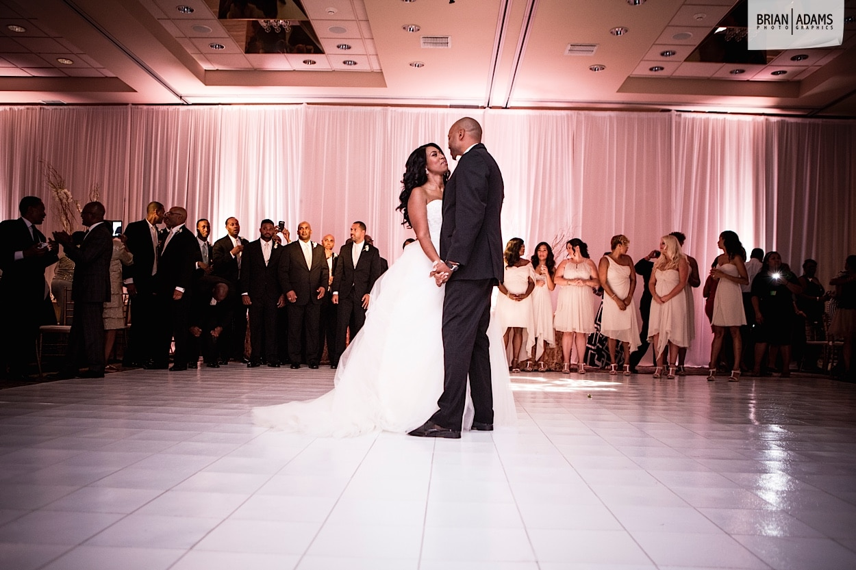 Bride and groom share first dance while wedding party looks on