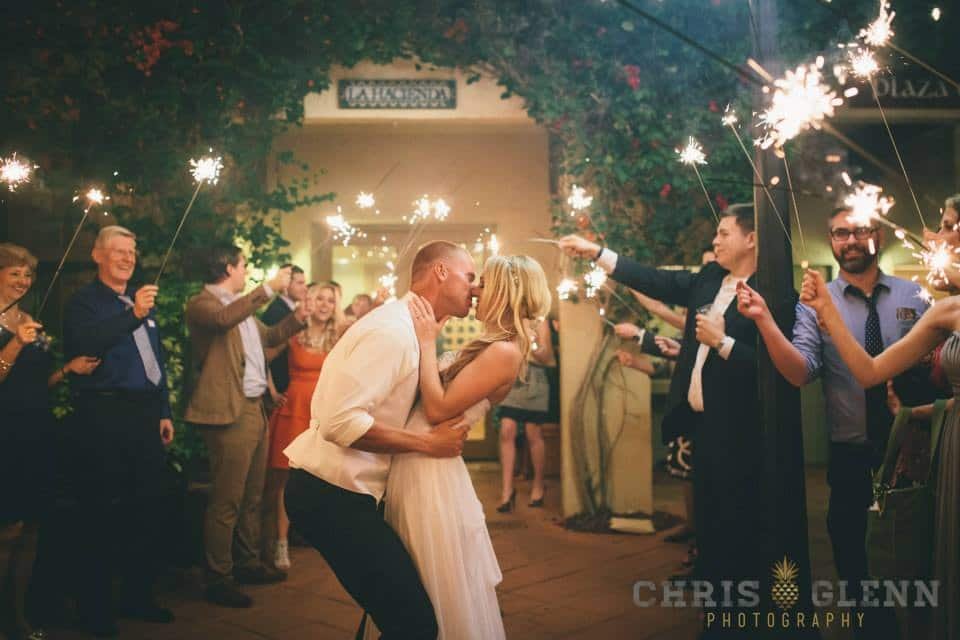 Bride and groom kiss during sparkler sendoff