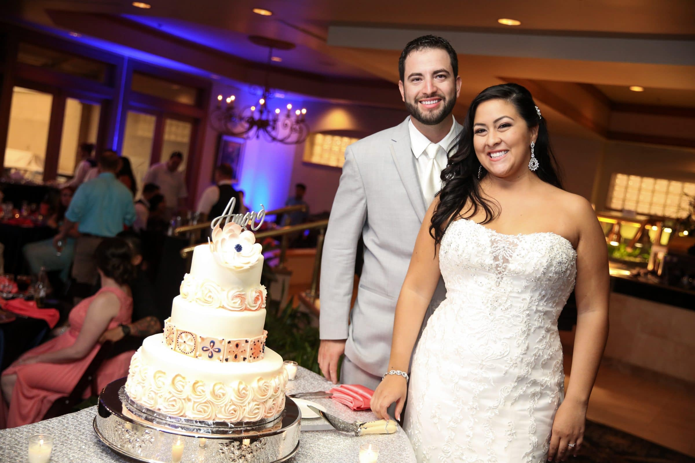 "Bride and groom next to unique Spanish-themed cake with ""tile"" fondant and Amor cake topper"