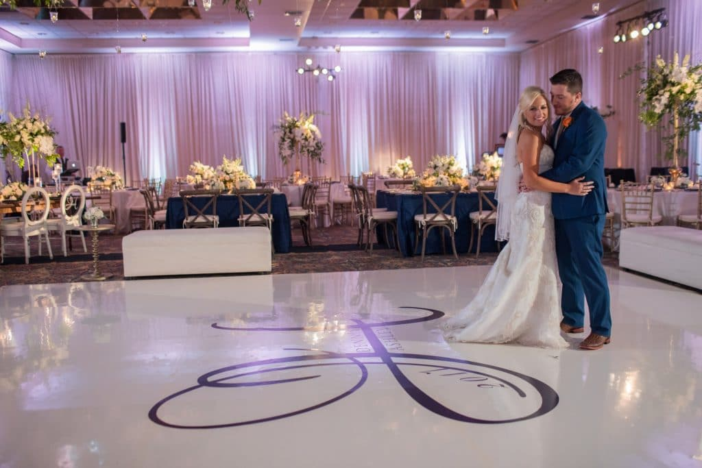 The Grand Ballroom - couple poses on customized, monogrammed dance floor