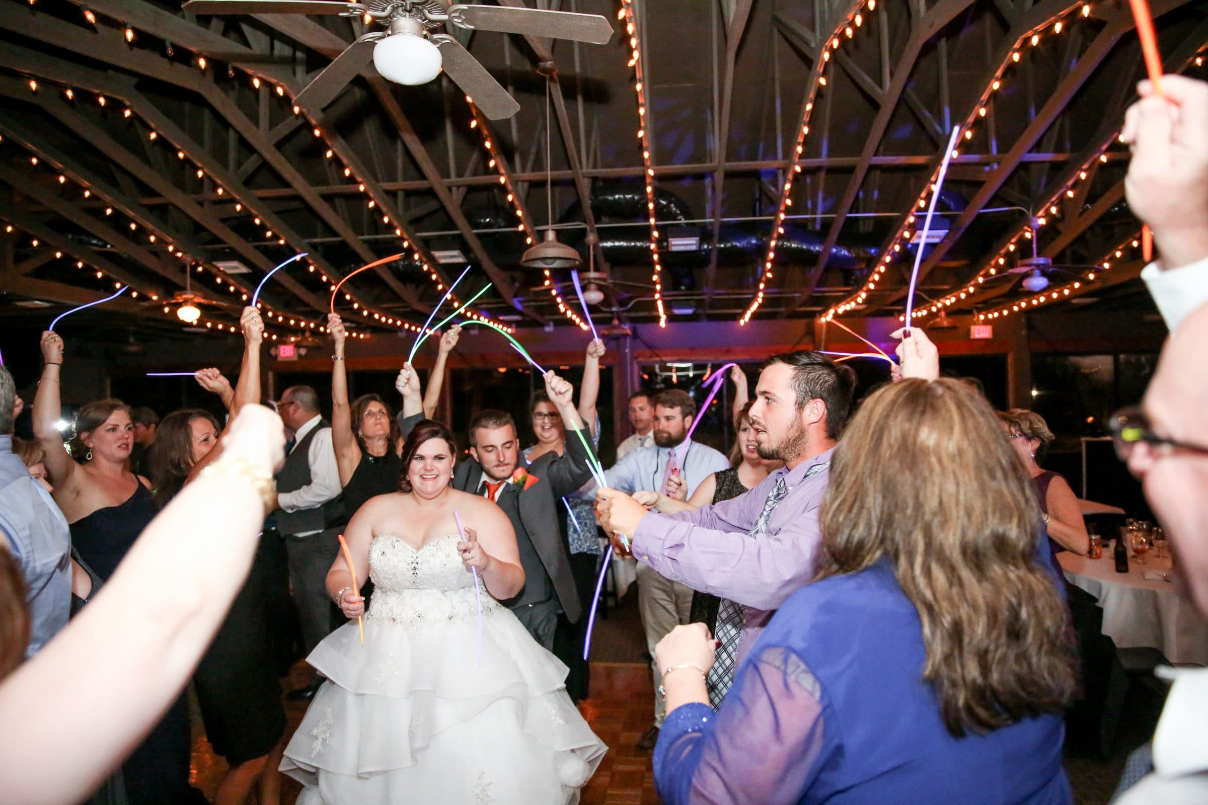 Bride and wedding guests waving glow sticks on the dance floor at Vista Lago