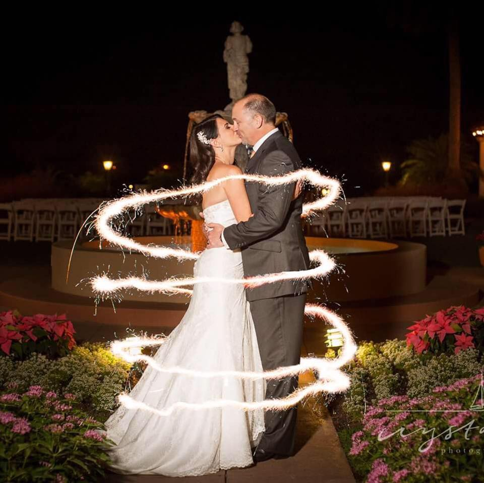 Bride and groom kissing by the fountain surrounded by ribbon of light