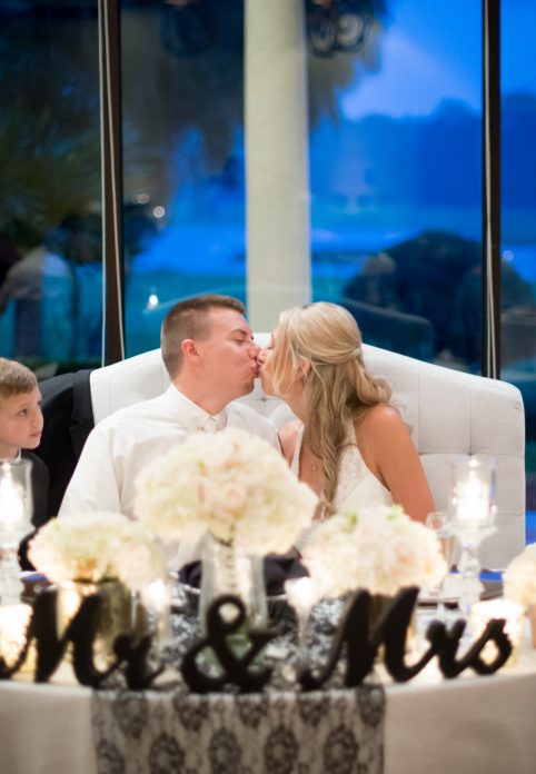 bride and groom kissing at sweetheart table in Legends Ballroom