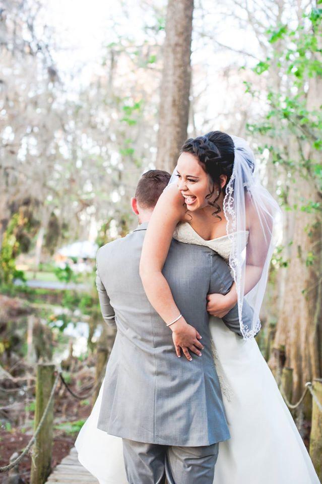 Bride laughing as she is held over groom's shoulder