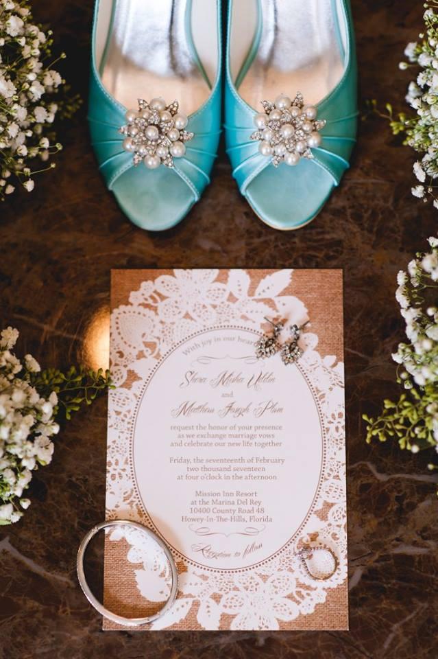 bridal jewelry sitting on wedding invitation