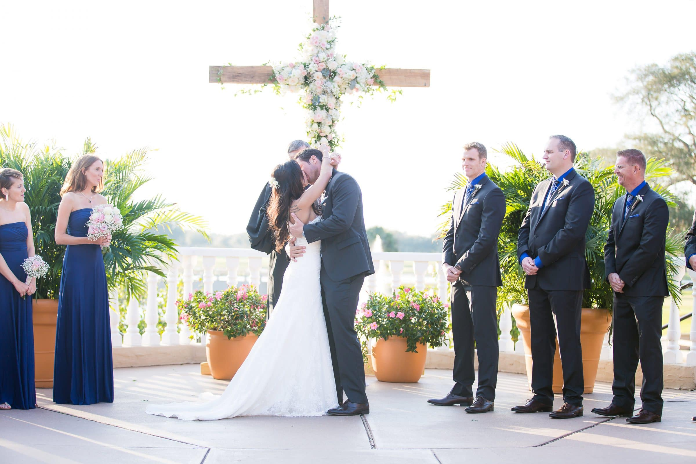 Bride and groom kiss in front of giant wooden cross decorated with flowers