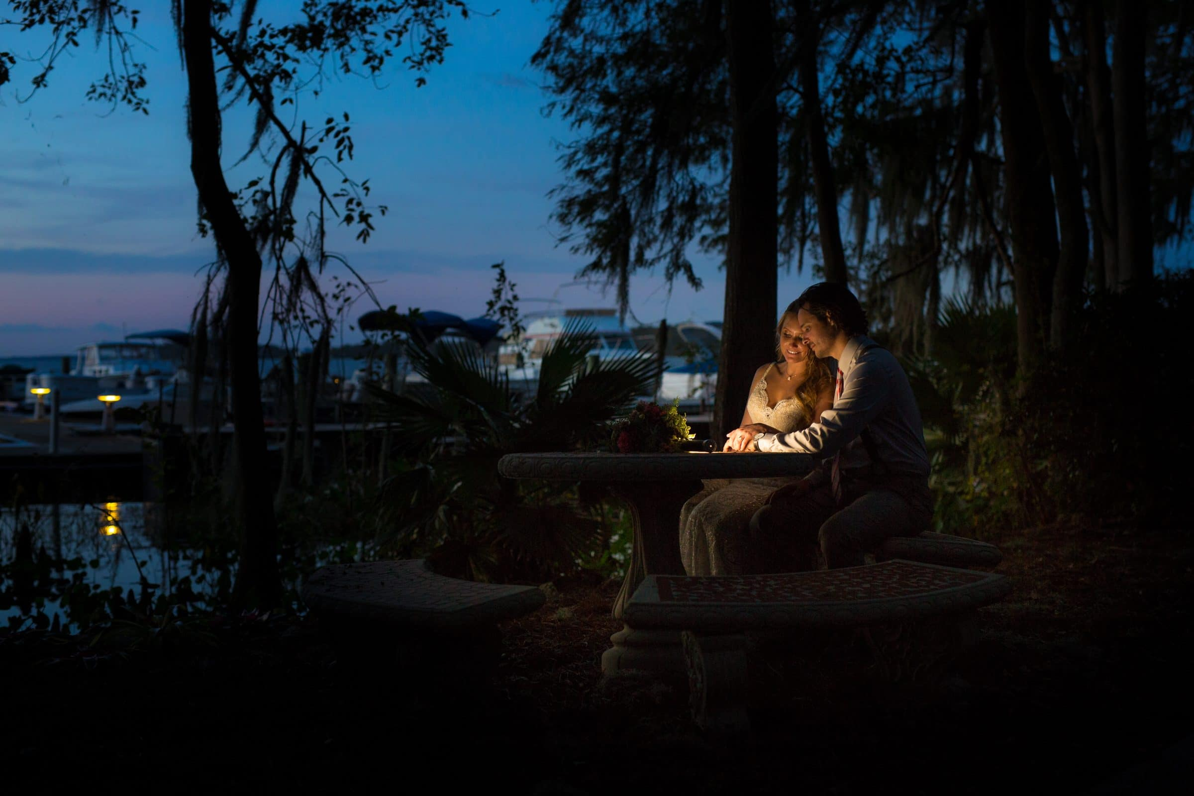 Bride and groom at lakeside table at night with dramatic uplighting