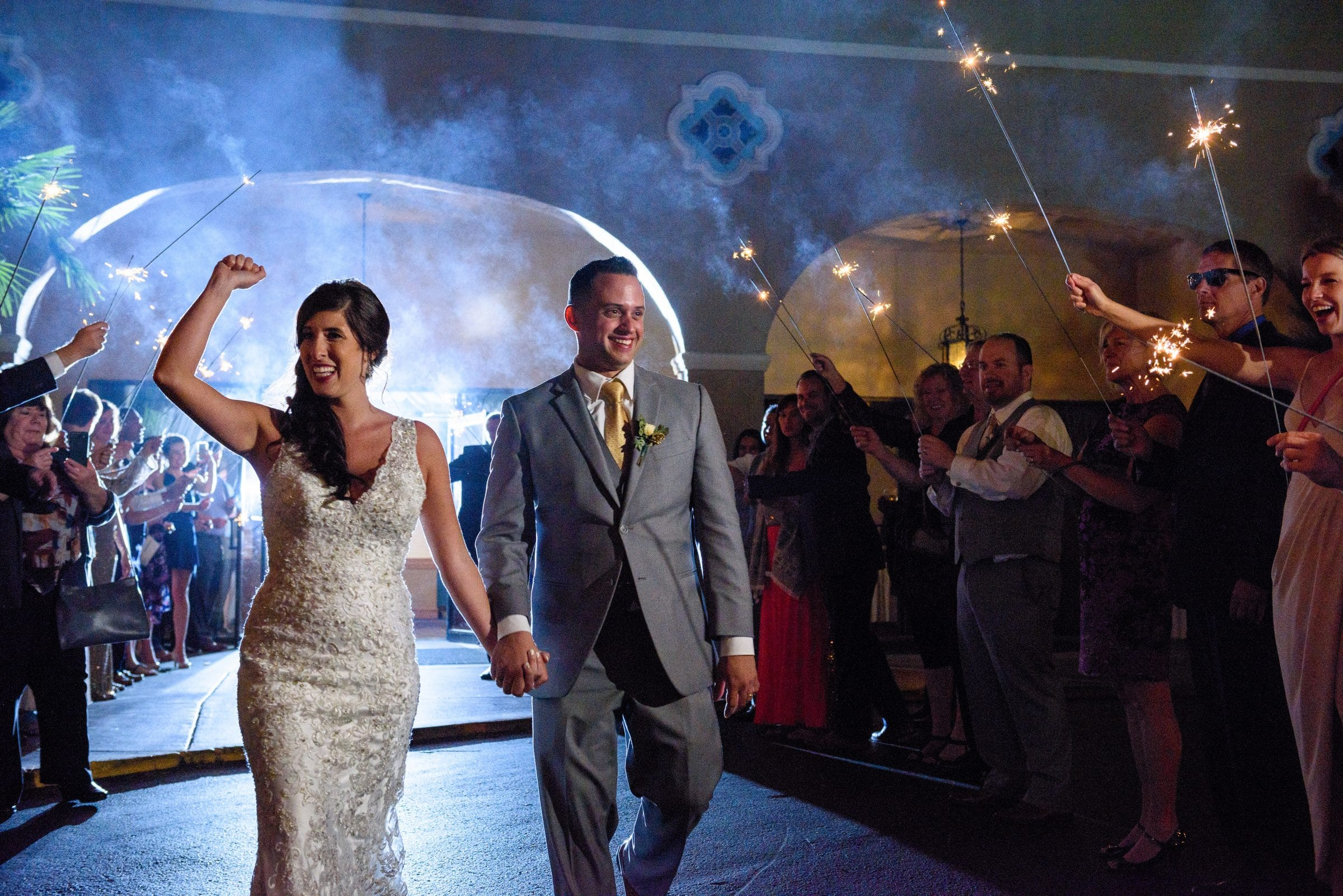 Bride and groom cheering during sparkler sendoff