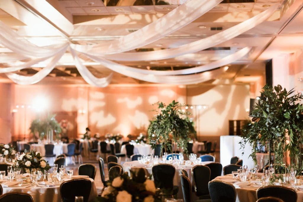 The Grand Ballroom - ballroom decorated with fabric ceiling drapes and greenery centerpieces