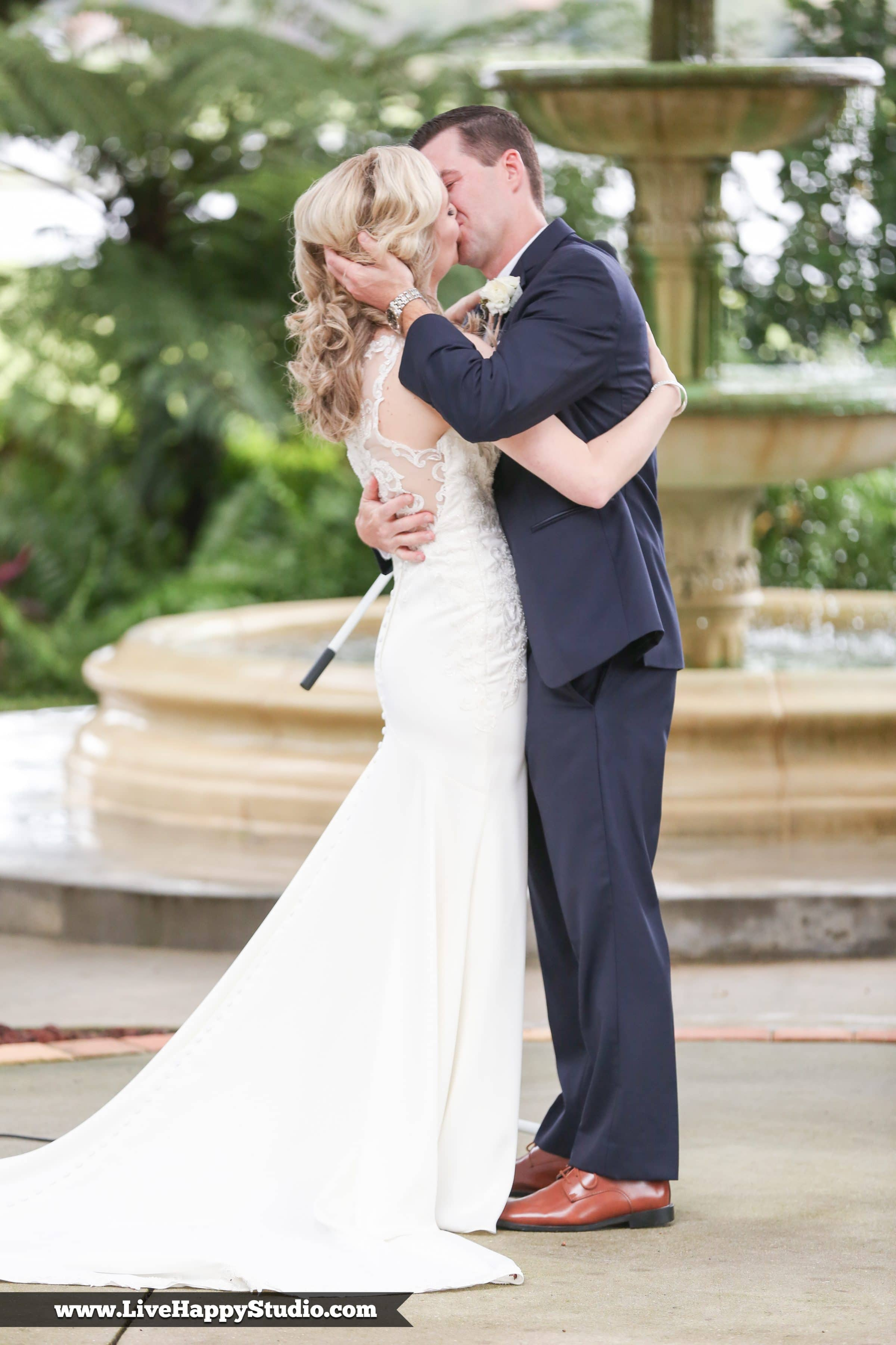Bride and groom kiss in front of fountain at Legends Courtyard