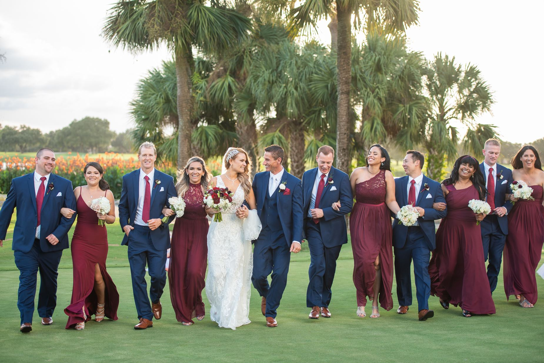 Wedding party in dark red dresses and navy suits walking Mission Inn golf course