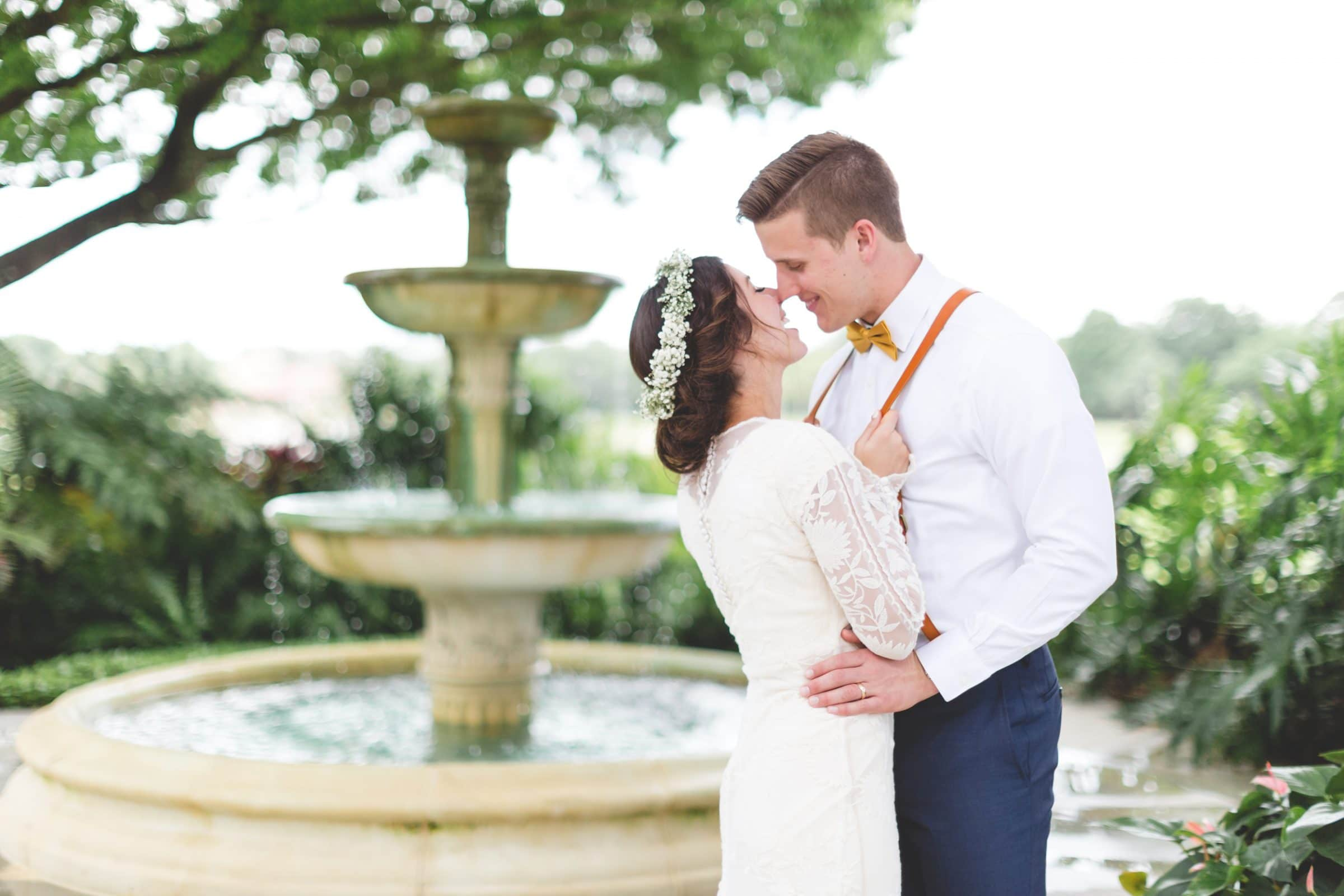 Boho bride and groom in front of vintage fountain narrowing down wedding venue search