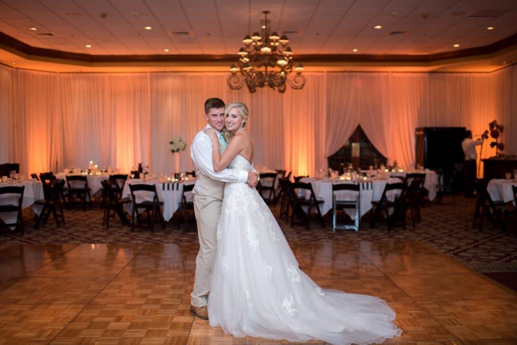 bride and groom posing on dance floor in empty Legends Ballroom