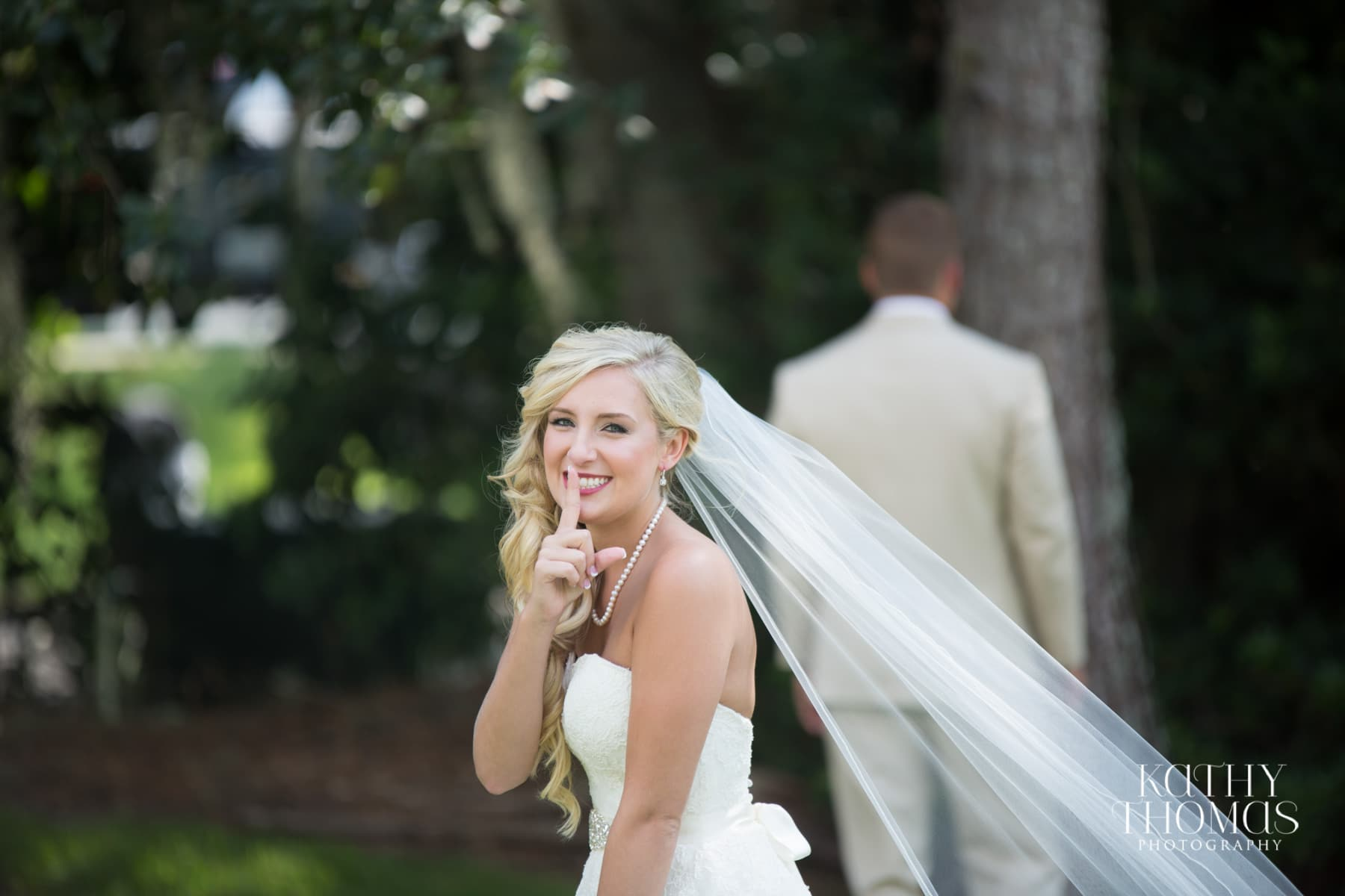 Bride with finger over mouth about to approach groom with back turned