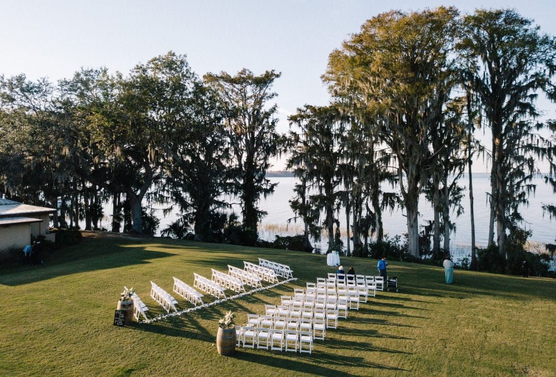 Wedding reception chairs set up in field overlooking lake