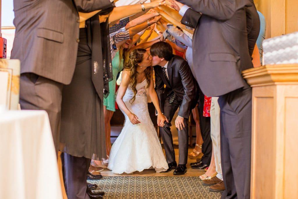 El Conquistador - bride and groom kissing through tunnel of guests